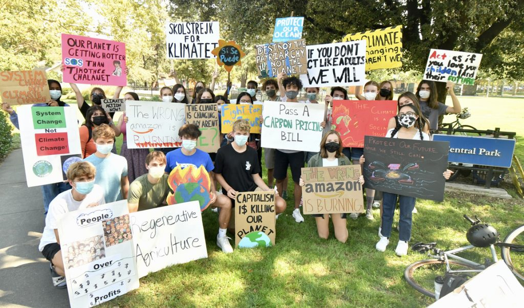 Students hold signs with powerful messages at the climate strike held at Davis Central Park Friday September 24, 2021. Photo credit: Johan Verink.