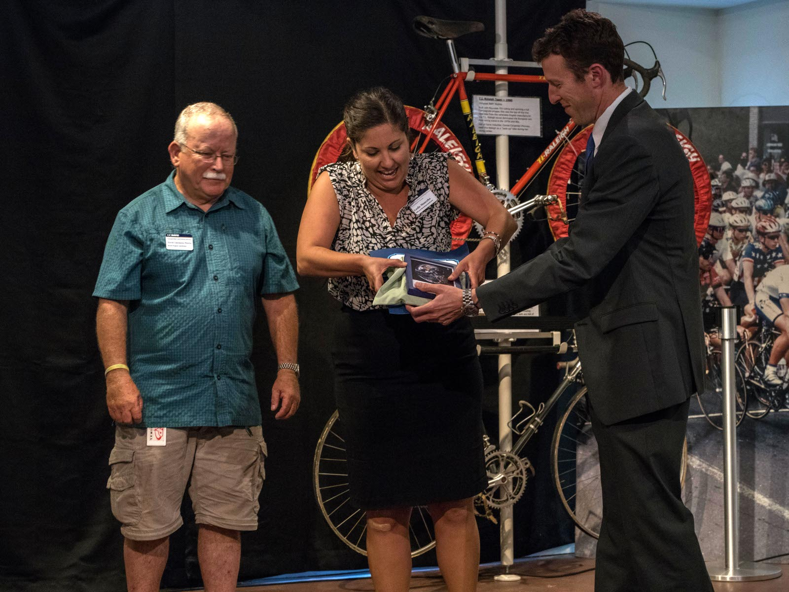 "While David Takamoto-Weerts looks on, Mayor Dan Wolk presents Leslie Mancebo with a Cool Davis Climate Solution Award for the achievements of the UC Davis Transportation Services. Leslie serves as Transportation Marketing Coordinator and David Takemoto-Weerts as bike coordinator for the department. Cool Davis honored Transportation Services' program for its ""goClub,"" which provides incentives and support to students and employees who choose to commute by bike, foot, bus, train, or carpool rather than use a single-occupant vehicle. With over 4,000 members in the goClub, Transportation Services has made UC Davis a national leader in the effort to cut carbon emissions."