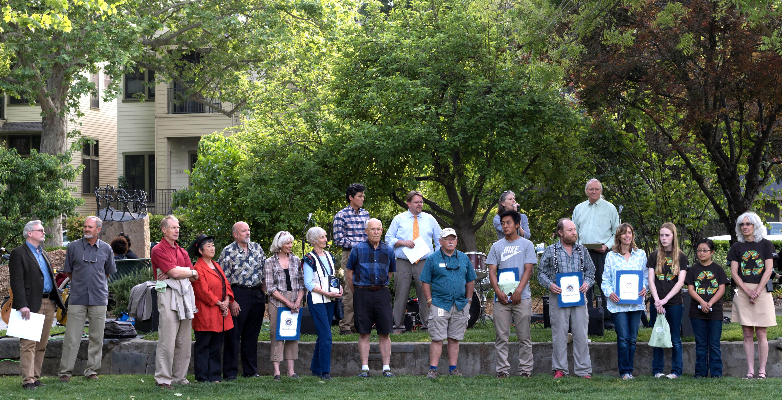 After the Cool Davis 2015 Awards were presented in the US Bicycling Hall of Fame, the whole group of awardees moved to the Davis Farmers Market Bandstand area, where Bill Heinicke, President of the Cool Davis Board and Chris Granger, Executive Director for the organization, gave introductory remarks before Councilmen Lucas Frerichs and Brett Lee introduced the whole group of awardees to those at the Market's Earth Day picnic.