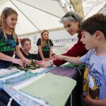 Emma Carney, 10; Sarah Carney, 12; and Sara Noren, 11; give away free veggie bags to Gina Bloom and her son Max, 6. Wayne Tilcock/Enterprise photo