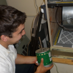 Greiner BPI certified tech Alex installing energy-efficient blower motor in furnace for PG&E customer under the Quality Maintenance program.