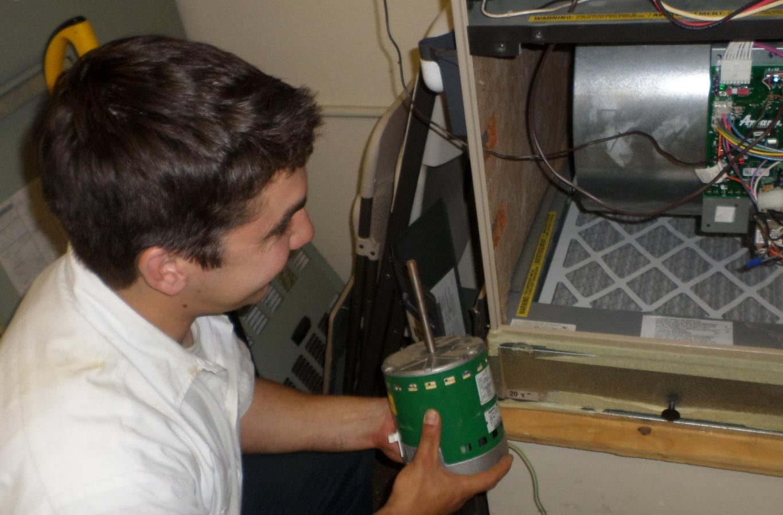 Greiner BPI certified tech Alex installing energy-efficient blower motor in furnace for PG&E customer under the Quality Maintenance program