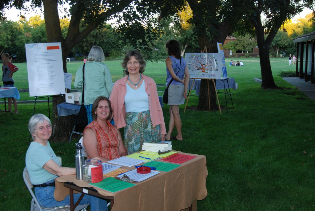 """Kerry Daane Loux of Cool Davis greets guests at """"Songs to Move the Earth"""" as presenter Lorraine Anderson looks on at the Village Homes Community Center."""