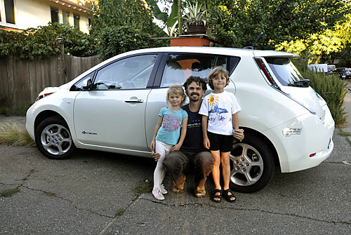 Peter Kerr and family show off their electric car, a Nissan Leaf